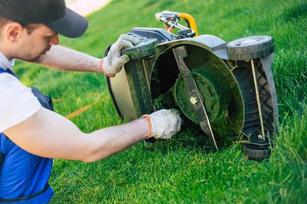 Jovem trabalhador em um terno especial limpa o cortador de grama elétrico da grama