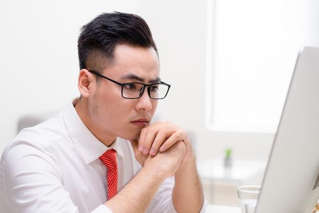 Jovem trabalhador estiloso no escritório trabalhando com computador e pensando em como resolver uma tarefa difícil