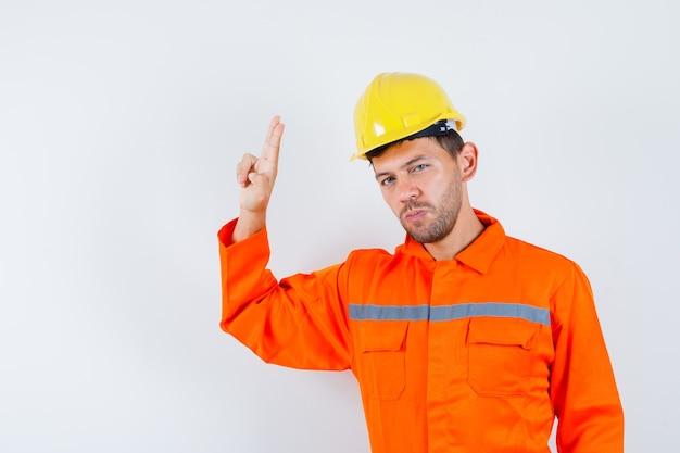 Jovem trabalhador gesticulando com a mão e os dedos de uniforme, capacete e parecendo confiante.