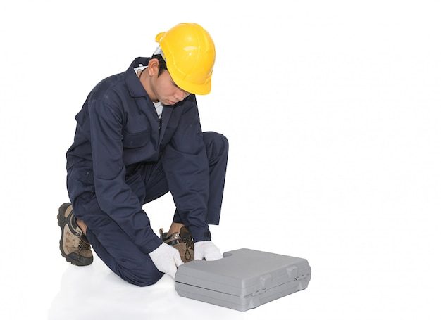 Jovem trabalhador manual sentado com sua caixa de ferramentas