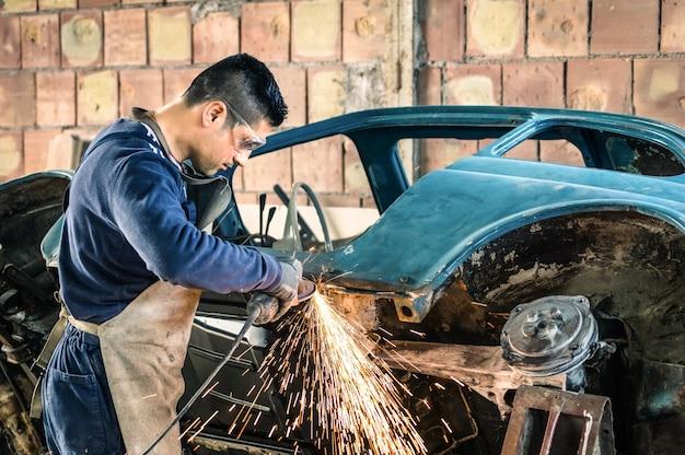 Jovem trabalhador mecânico consertando uma carroceria de carro antigo em uma garagem bagunçada