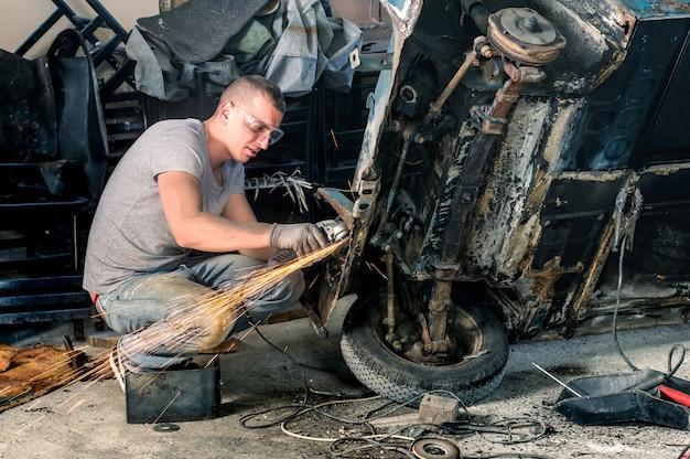 Jovem trabalhador mecânico consertando uma carroceria de um carro antigo em uma garagem bagunçada