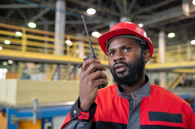 Jovem trabalhador negro barbudo com uniforme vermelho transferindo mensagem para um colega de trabalho com um dispositivo de walkie-talkie no canteiro de obras