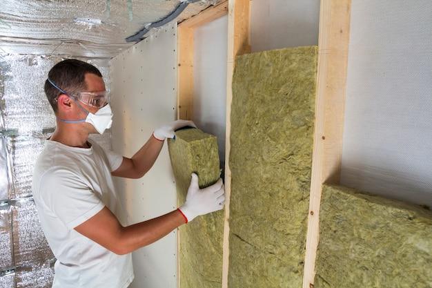Jovem trabalhador no pessoal de isolamento de lã de rocha do respirador no quadro de madeira para paredes futuras da casa para barreira fria. confortável casa quente, economia, construção e conceito de renovação.