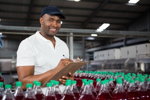 Jovem trabalhador observando em fábrica de suco