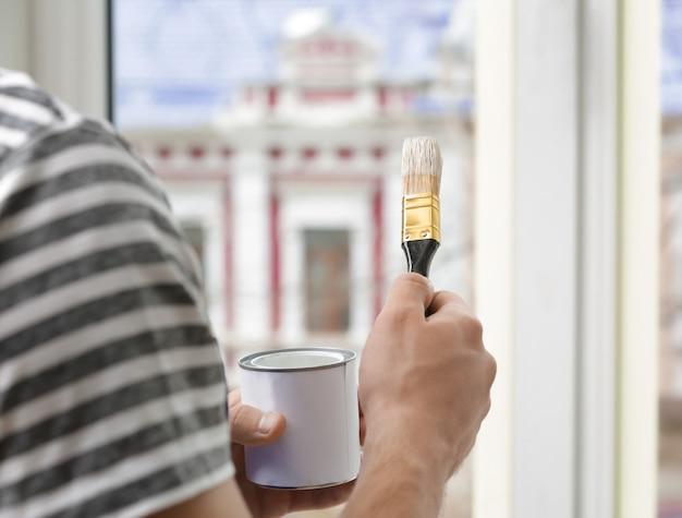 Jovem trabalhador pintando janela no escritório, close-up