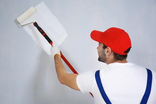 Jovem trabalhador pintando parede na sala