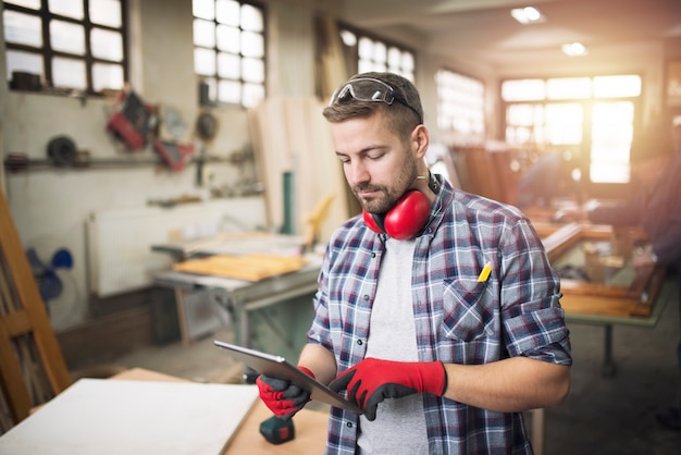 Jovem trabalhador profissional carpinteiro com óculos de proteção, segurando um tablet e verificando o design de seu projeto na oficina