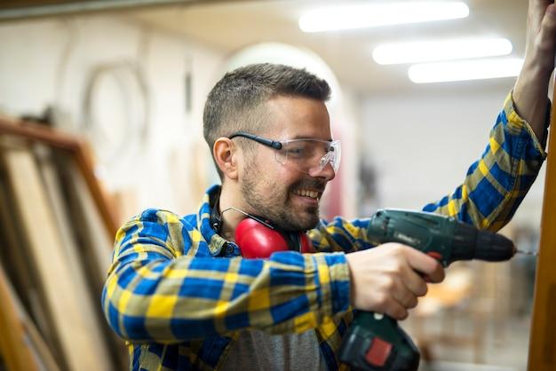 Jovem trabalhador profissional carpinteiro com óculos de proteção, segurando uma furadeira e trabalhando em seu projeto na oficina