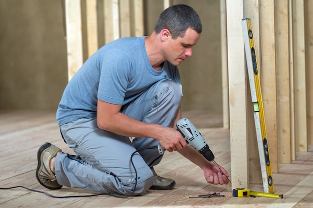 Jovem trabalhador profissional usa nível e chave de fenda para instalar a moldura de madeira para futuras paredes. interior da sala do sótão com piso de carvalho em reconstrução. conceito de renovação e melhoria.