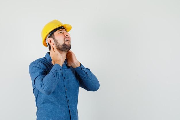 Jovem trabalhador que sofre de dor no pescoço na camisa, capacete e parece cansado.