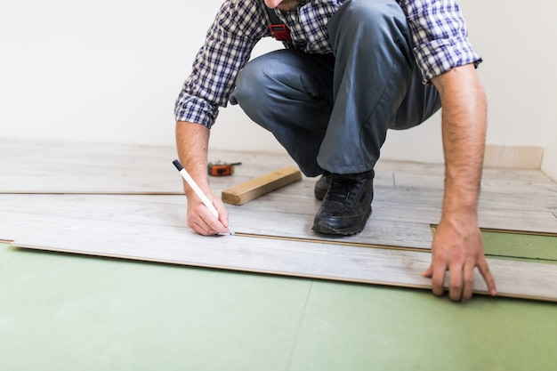 Jovem trabalhador revestindo um piso com tábuas de piso laminado