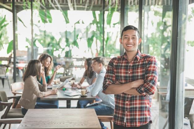 Jovem trabalhador se encontrando em um café com seu trabalho em equipe