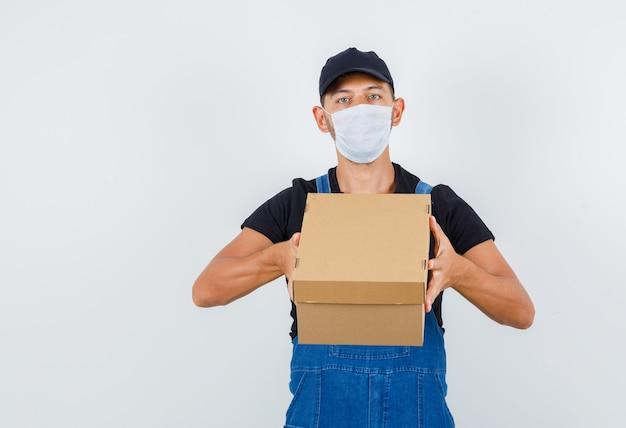 Jovem trabalhador segurando a caixa de papelão em uniforme, máscara, vista frontal.
