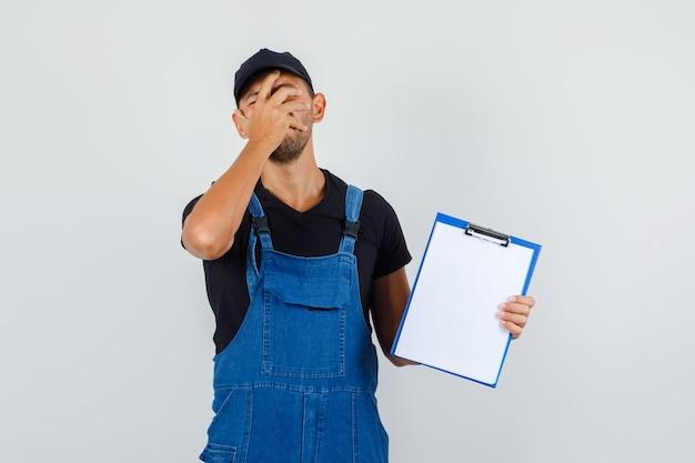 Jovem trabalhador segurando a prancheta com a mão cobrindo o rosto de uniforme e parecendo triste. vista frontal.