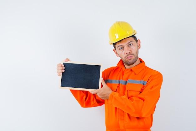 Jovem trabalhador segurando o quadro-negro de uniforme, capacete.