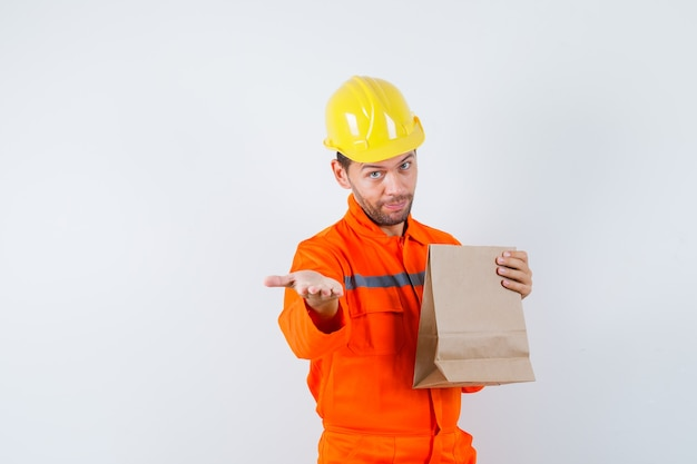 Jovem trabalhador segurando um saco de papel, esticando a mão de uniforme.
