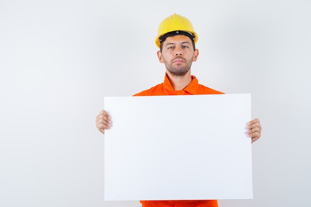 Jovem trabalhador segurando uma tela em branco de uniforme, capacete e parecendo confiante.