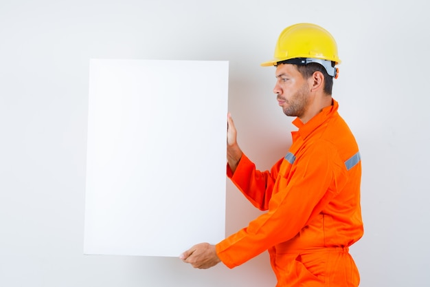 Jovem trabalhador segurando uma tela em branco de uniforme, capacete.