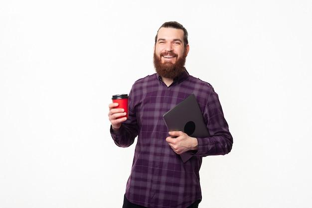 Jovem trabalhador segurando uma xícara de café e um laptop