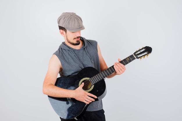 Jovem trabalhador tocando guitarra com uma camiseta cinza e boné e olhando focado