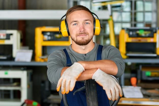 Jovem trabalhador vestindo capas protetoras para as orelhas