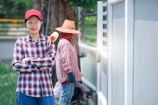 Jovem trabalhadora asiática pintando a parede da casa com a mão e pincel de rolo de pintura tinta que é cinza ou tinta de cimento