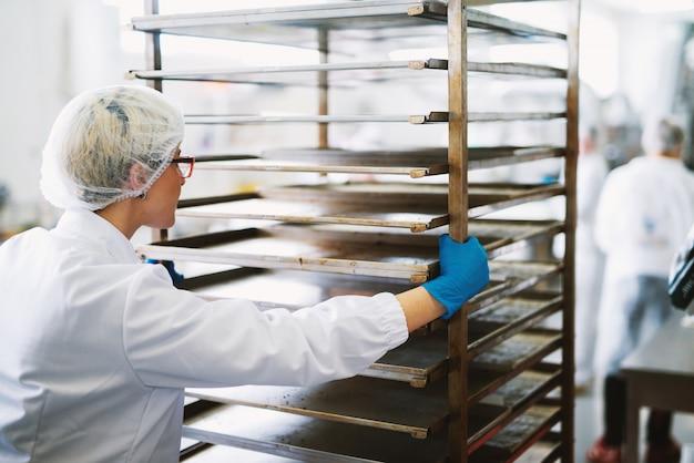 Jovem trabalhadora bonita em panos estéreis está empurrando as prateleiras com panelas sujas para limpeza.
