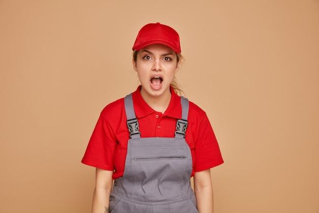 Jovem trabalhadora da construção civil animada usando uniforme e boné