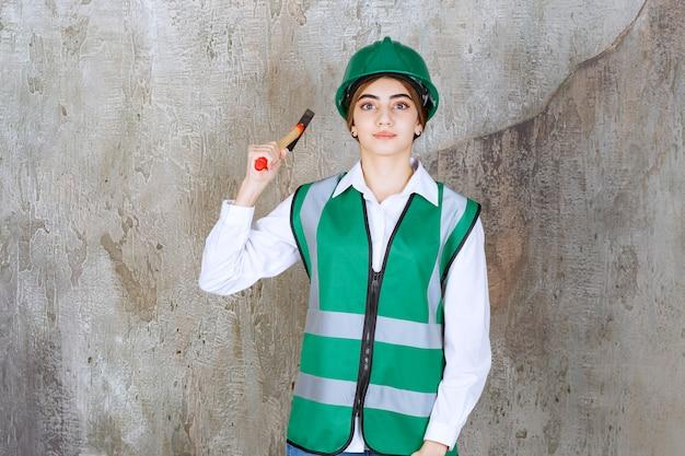 Jovem trabalhadora da construção civil com capacete verde posando com um martelo