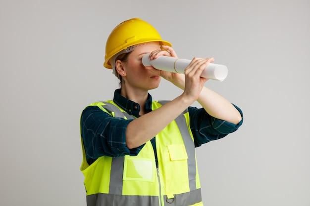 Jovem trabalhadora da construção civil séria usando capacete de segurança e colete de segurança segurando papel e usando como telescópio