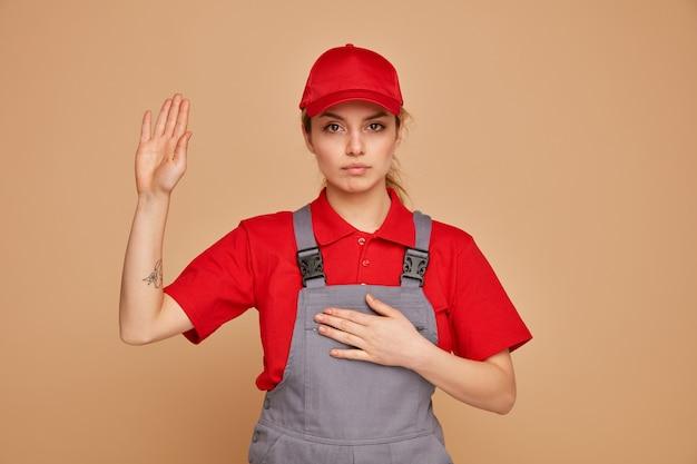 Jovem trabalhadora da construção civil séria vestindo uniforme e boné fazendo gesto de promessa