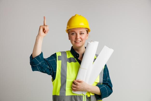 Jovem trabalhadora da construção civil sorridente usando capacete e colete de segurança segurando papéis apontando para cima