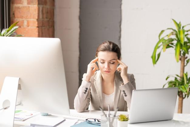Jovem trabalhadora de escritório cansada em trajes formais tocando suas têmporas enquanto tenta se concentrar durante o trabalho no computador