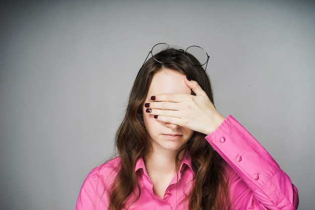 Jovem trabalhadora de escritório com uma camisa rosa cobrindo os olhos com as mãos