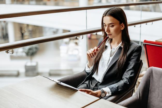 Jovem trabalhadora de escritório ou empresária assina documentos
