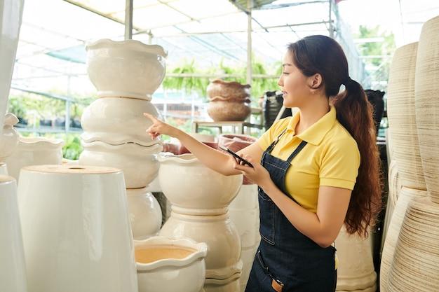 Jovem trabalhadora de estufa com smartphone nas mãos, preparando grandes potes de barro para vender no centro de jardinagem