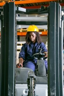 Jovem trabalhadora de logística focada em capacete operando empilhadeira em armazém, puxando a alavanca