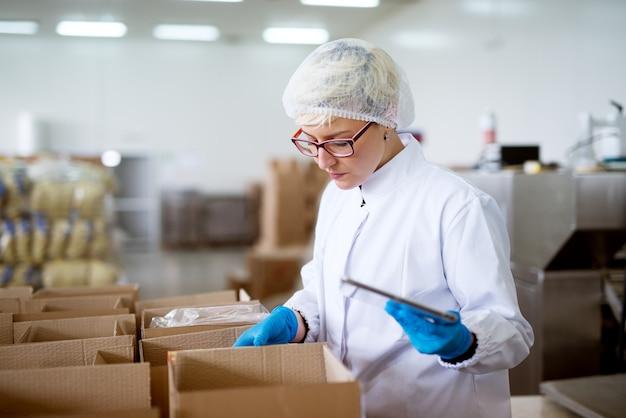 Jovem trabalhadora em causa linda em panos estéreis, usando um tablet para verificar a correção do inventário dentro de caixas no depósito da fábrica.