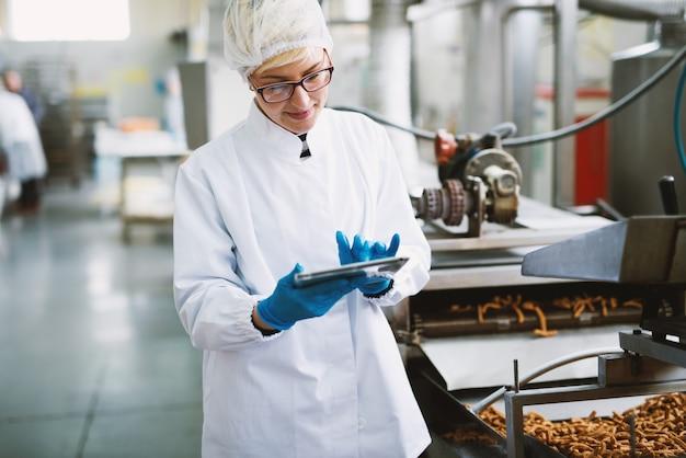 Jovem trabalhadora em roupas estéreis está verificando a qualidade dos produtos na fábrica de alimentos.