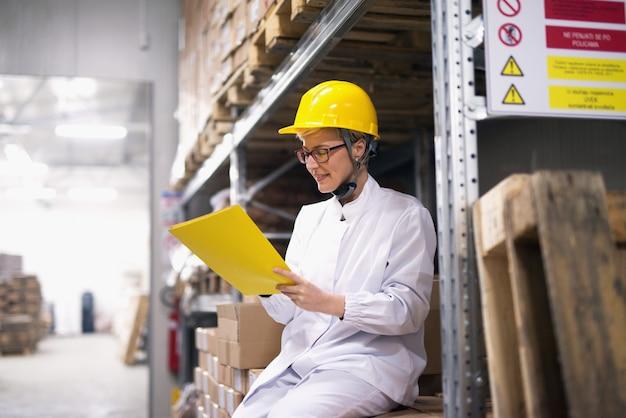 Jovem trabalhadora está sentado na sala de armazenamento e verificação de documentos.