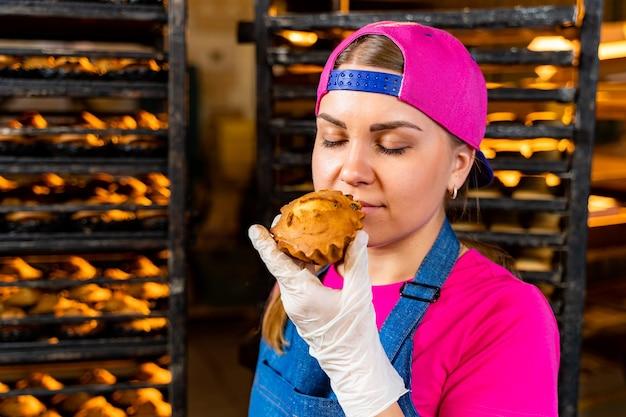 Jovem trabalhadora feliz em panos estéreis, segurando bolinhos recém-assados nas mãos, dentro da fábrica de produção de alimentos.