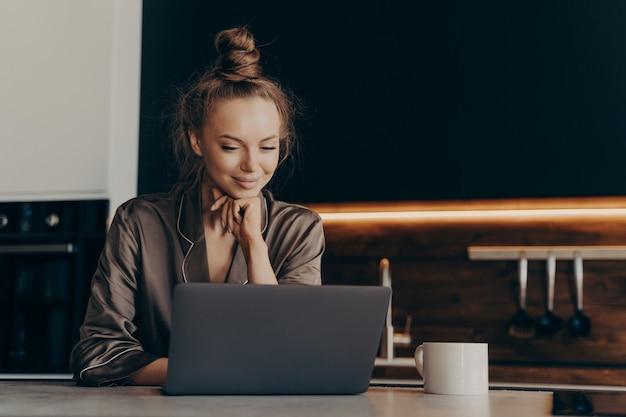 Jovem trabalhadora freelance feminina de pijama bebe café da manhã para um trabalho produtivo bem sucedido começar enquanto está sentado na cozinha com o laptop e verificando e-mails. trabalho remoto e conceito freelance