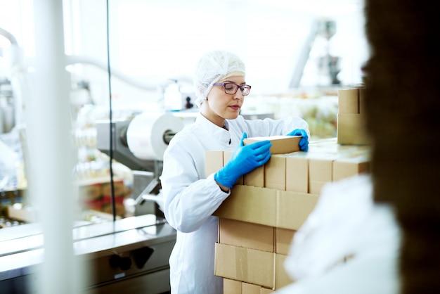 Jovem trabalhadora linda e focada em panos estéreis está colocando a última caixa em uma grande pilha de caixas de papelão perto da linha de produção da fábrica de alimentos.