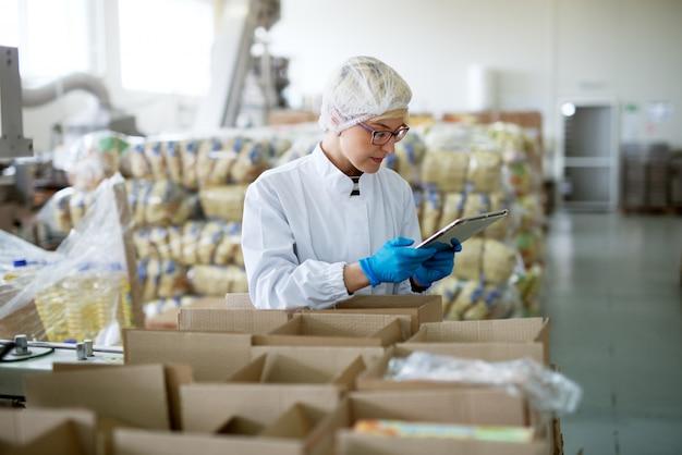 Jovem trabalhadora profissional bonita em panos estéreis está usando um tablet dentro de uma sala de armazenamento de fábrica enquanto está encostado em caixas.