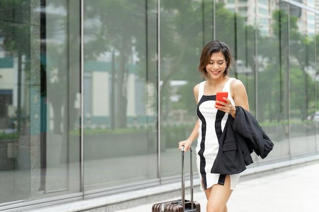 Jovem trabalhadora usa smartphone e caminha com mala