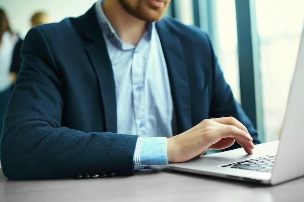 Jovem trabalhando com laptop, as mãos do homem no computador portátil, pessoa de negócios no local de trabalho