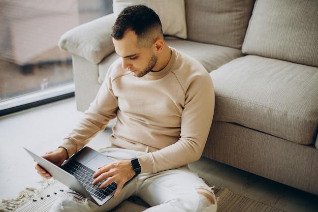 Jovem trabalhando em casa em um laptop