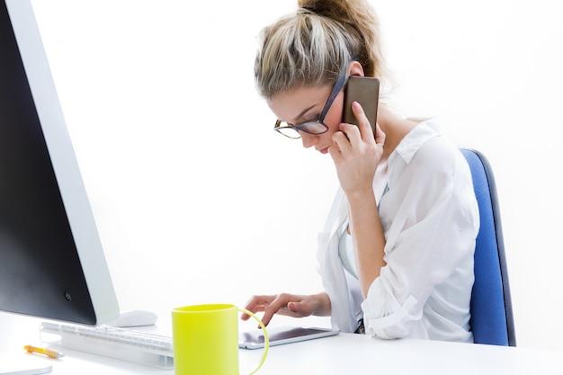 Jovem trabalhando em casa no computador e falando ao telefone com o escritório