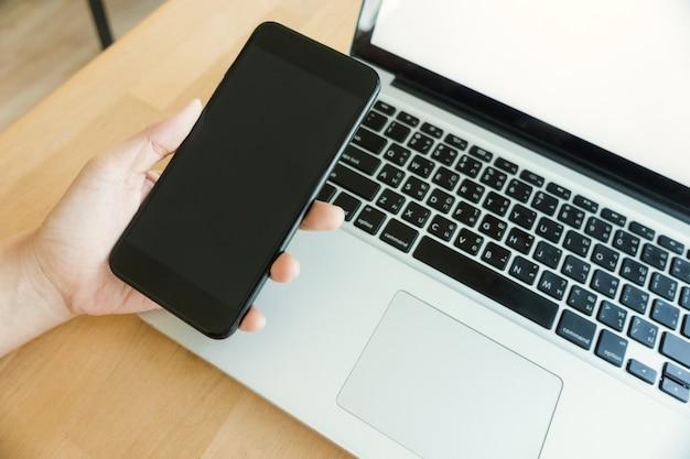 Jovem trabalhando em casa usando maquete de telefone inteligente e laptop